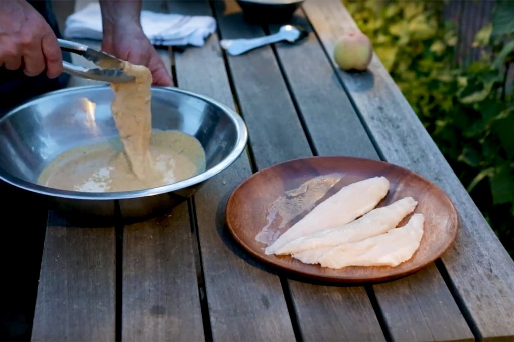Placing catfish fillets into the cornmeal batter