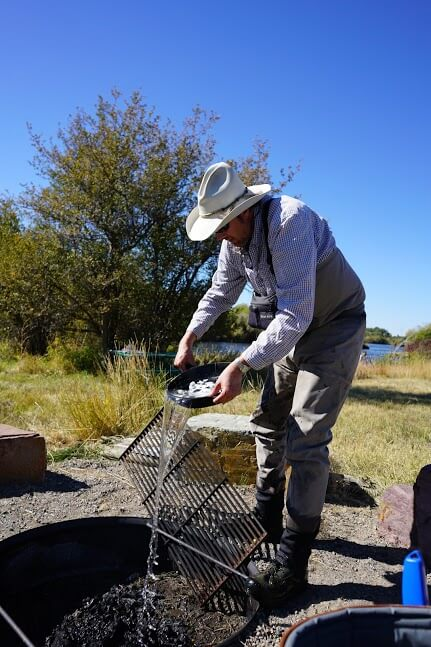 Guide Tom Grimes helps clean cast iron and extiguish the fire at one time