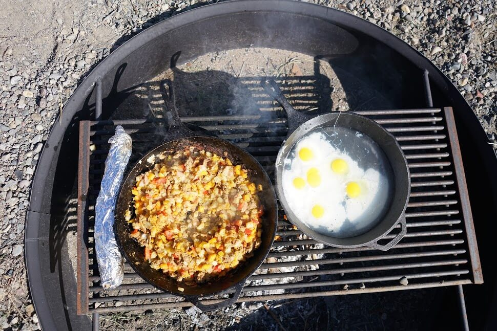 Poached Eggs and Red Flannel Hash Cooking over an open fire in cast iron skillets