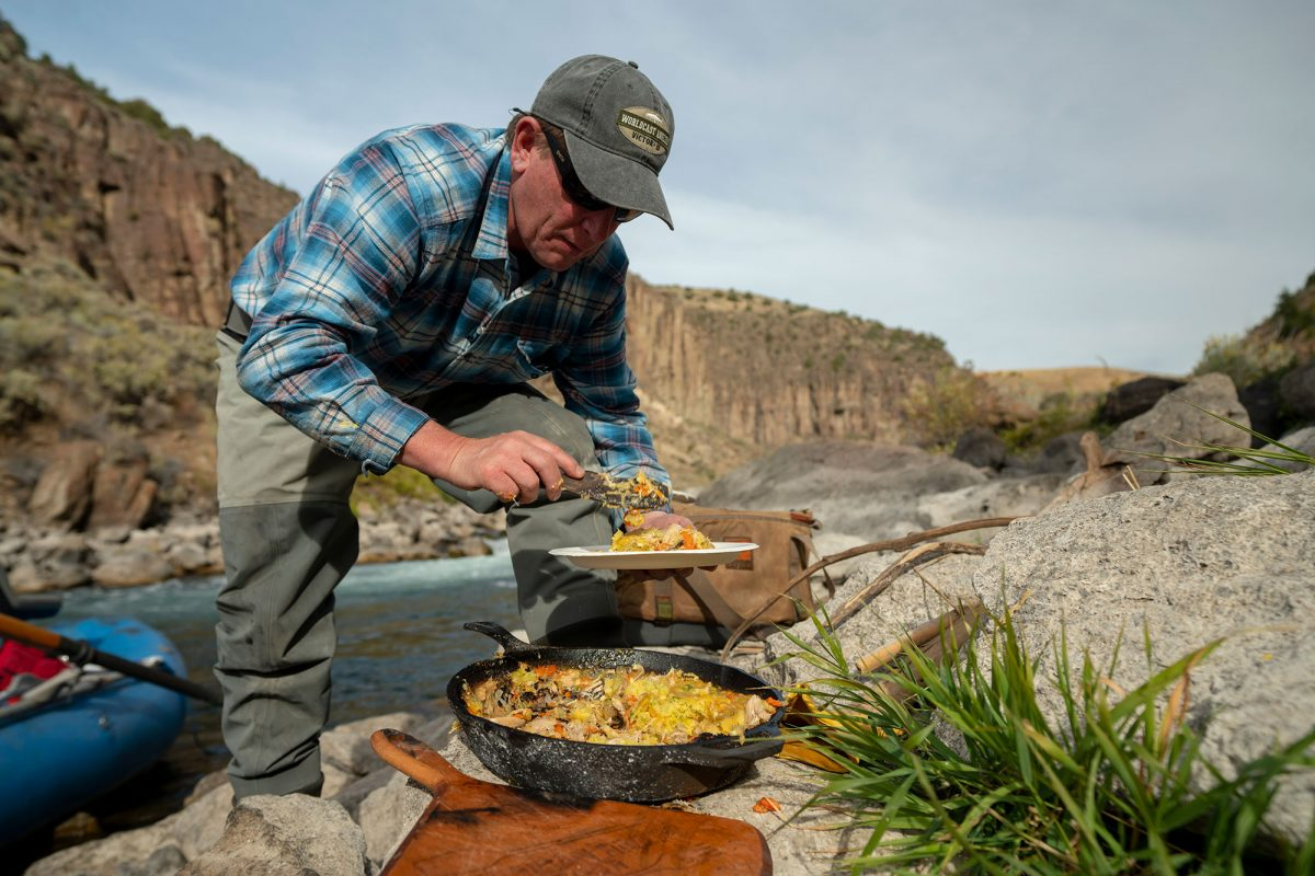 Colin serving cornbread crusted chicken pot pie by the Teton river